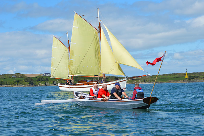 (l-r) Liam O'Donoghue, Anthony Kenny and Robert Smalle row past sailing ketch Síle A Dó